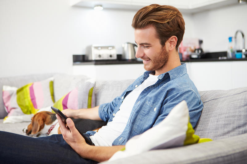 Download Young Man With Dog Sitting On Sofa Using Digital Tablet Stock Image - Image: 40094899