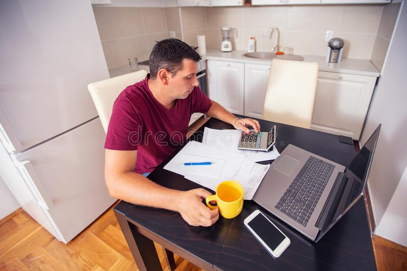 Young man doing account about expenses at home, family budget an royalty free stock photo