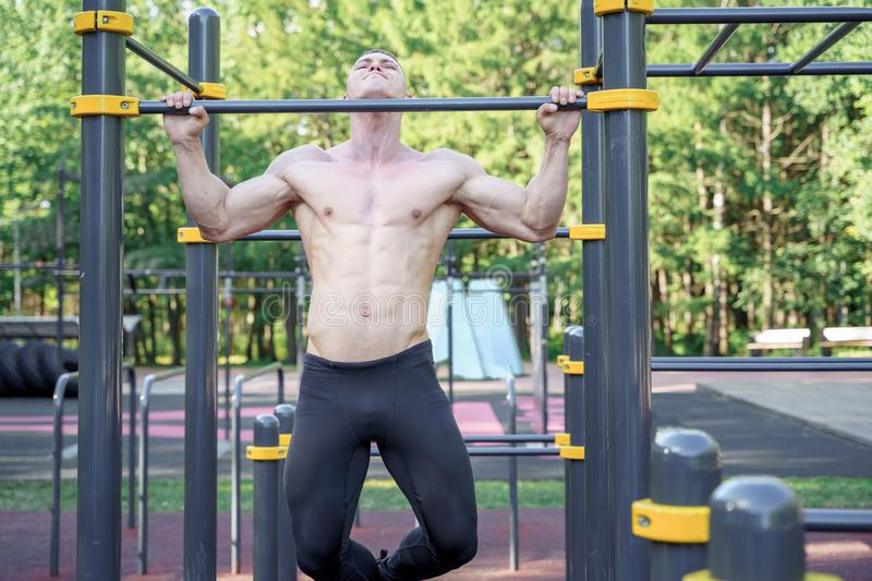 Young man doing exercise on a horizontal bar outdoors.  stock photography