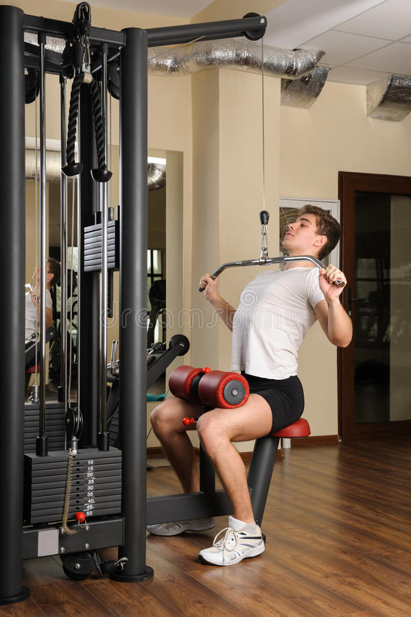 Young man doing lats pull-down workout royalty free stock photography