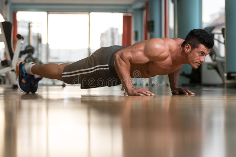 Young Man Doing Press Ups In Gym. Young Adult Athlete Doing Push Ups As Part Of Bodybuilding Training stock images