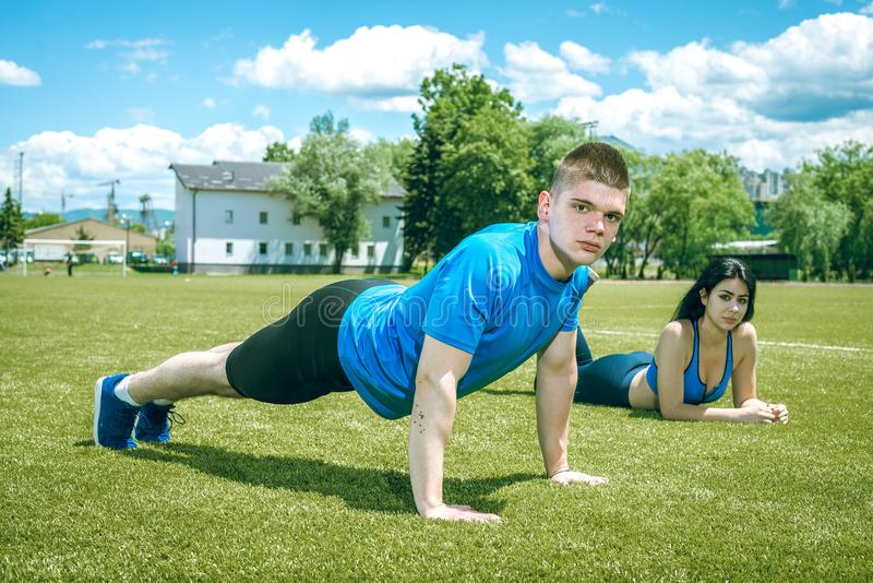 Young man doing push ups outdoor in grass. Young athlete doing push ups outdoor on grass football field together with his female partner during hot summer day stock photo