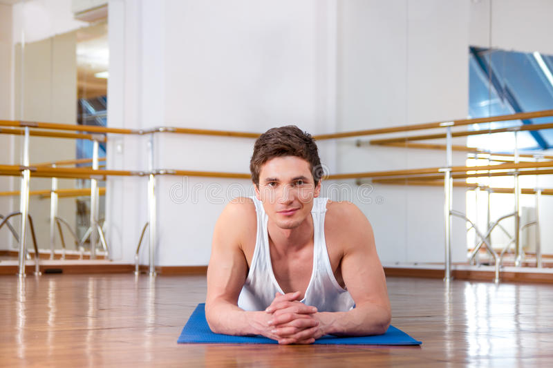 Young man doing sit ups in the fitness studio stock photos