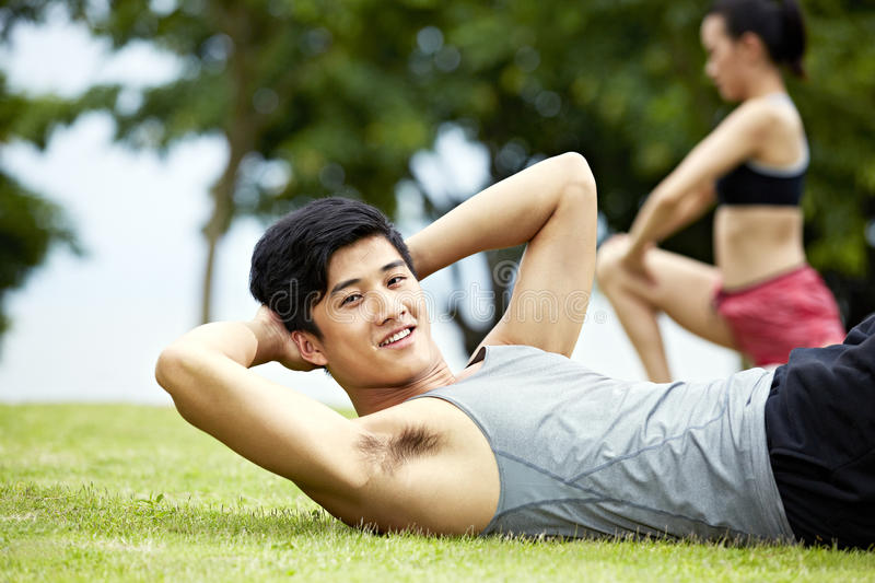 Young man doing sit-ups in park stock photography