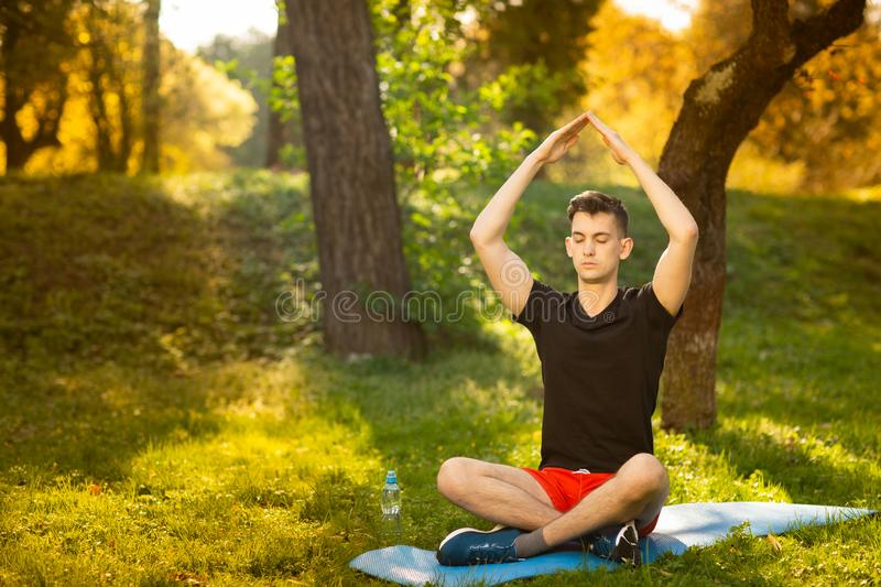 A young man doing yoga in the green park. Concept of a healthy lifestyle stock photography