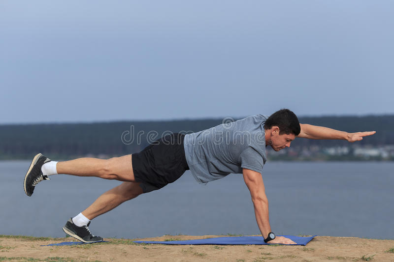 Young man doing yoga outside in natural environment.  royalty free stock photography