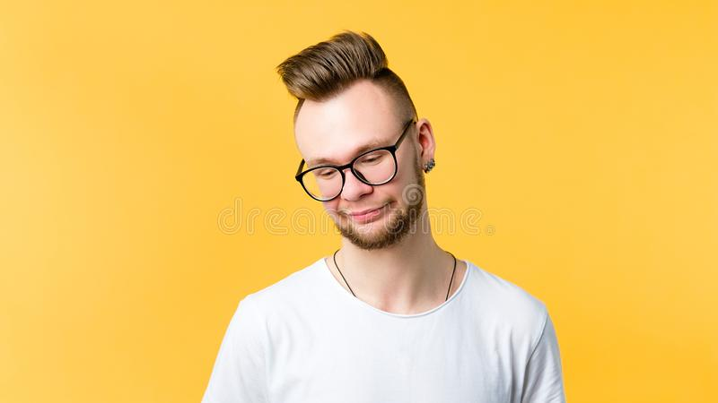 Young man doubt skepticism wary look emotion. Young man looking down. Doubt skepticism facial expression. Pursed lips. Suspicious incredulous wary bored look royalty free stock image