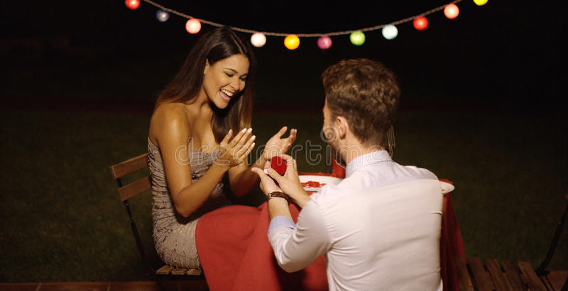 Young man down on his knees proposing. Young men down on his knees proposing to his loved one offering her the ring in a box as she reacts with joyful surprise stock photo