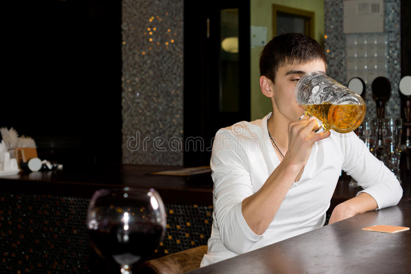 Young man downing a large tankard of beer royalty free stock photography