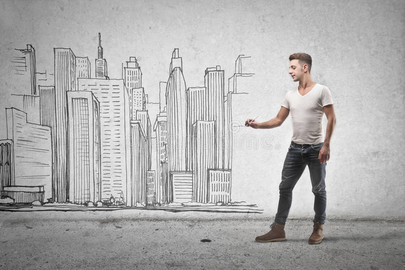 Young man drawing a building royalty free stock photos
