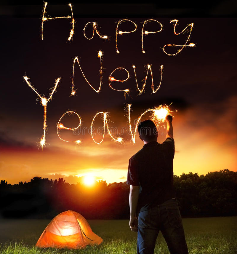 Young man drawing happy new year words by sparkling stick. Camping on the mountain stock photography