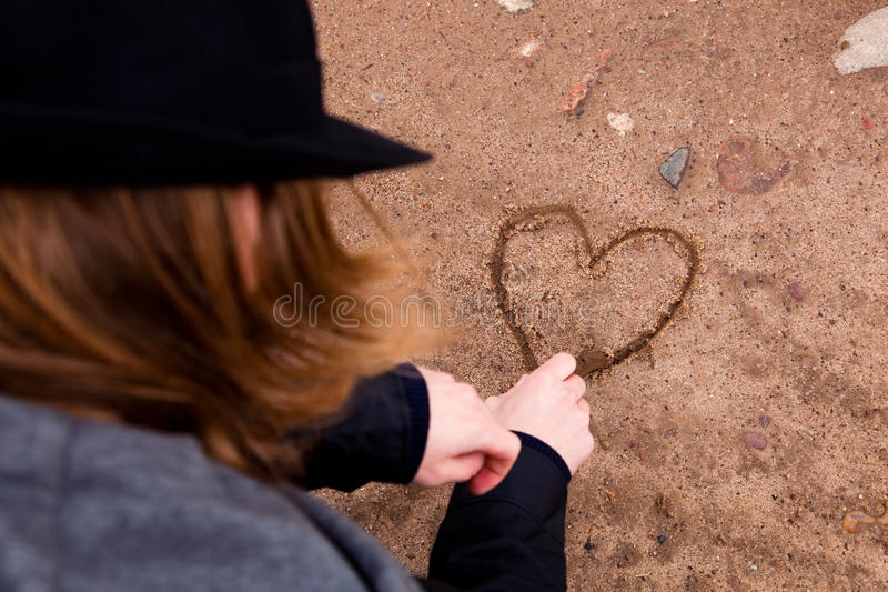 Young man drawing heart. Young man drawing a heart shape on ground stock photos