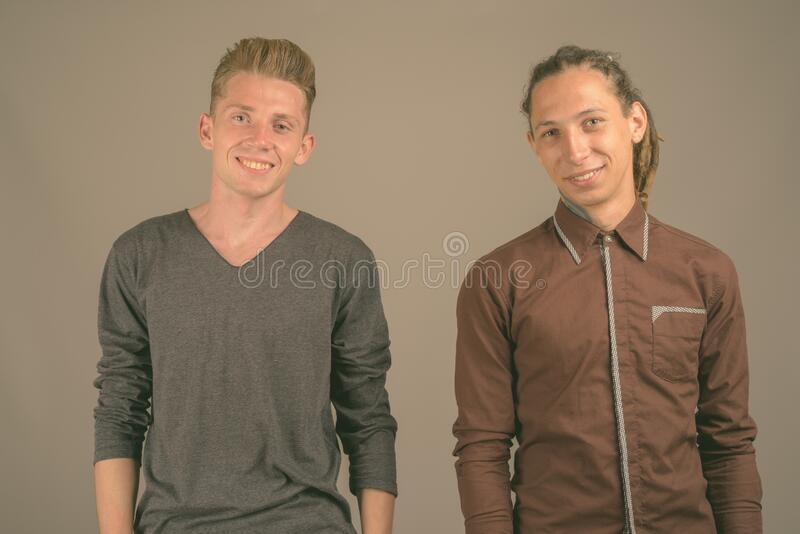 Young man with dreadlocks and young man with blond hair against gray background stock photos
