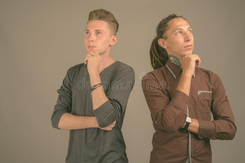 Young man with dreadlocks and young man with blond hair against gray background stock photography