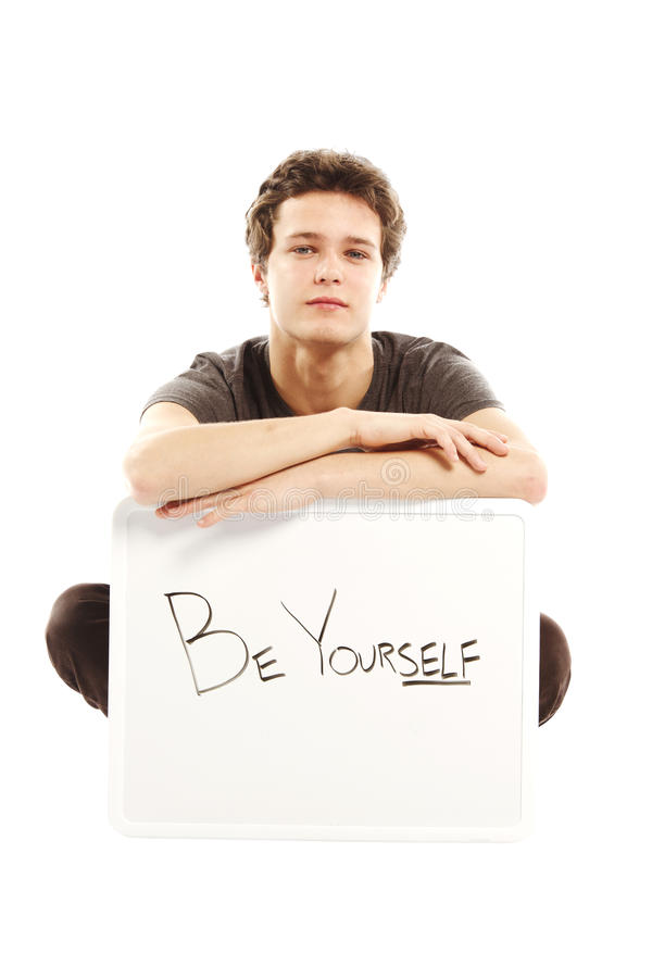 Young man dressed in hip style holding sign. Young man dressed with hip style holding sign that says be yourself royalty free stock photography