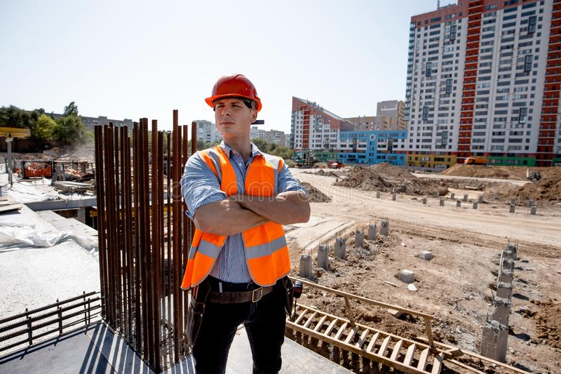 Young man dressed in shirt, orange work vest and helmet stands on the building site against the background of a multi royalty free stock photo