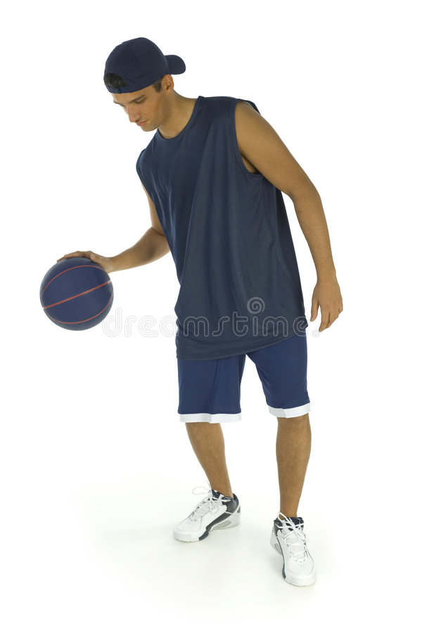 Young man dribbling basketball. Young man playing in basketball. He's dribbling. Isolated on white background stock images