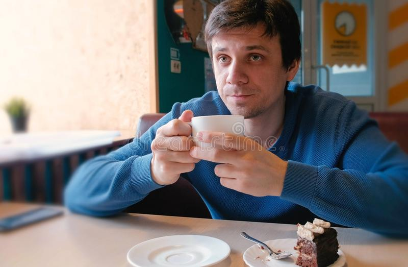 Young man drink a tea in cafe. royalty free stock photos