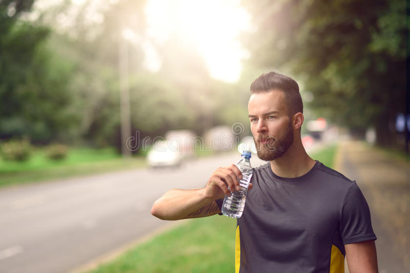 Young man drinking bottled water. Young man with a beard drinking bottled water as he walks down a tree lined avenue in a park, close up head and shoulders stock photo