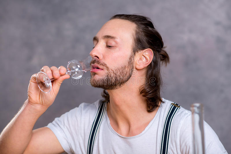 Young man drinking clear spirit royalty free stock images