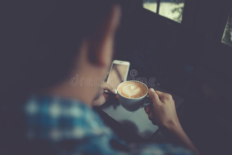 Young man drinking coffee cup in cafe and looking at phone scree stock images