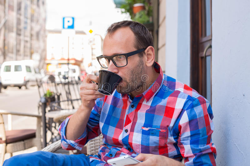 Download Young Man Drinking Coffee In Restaurant. He Is Holding A Mobile Phone. Stock Image - Image: 34065423