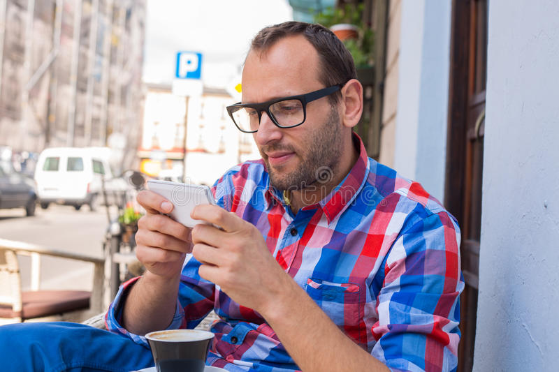 Download Young Man Drinking Coffee In Restaurant. He Is Holding A Mobile Phone. Stock Photo - Image: 34065790