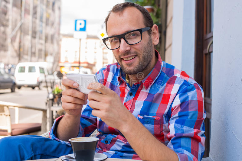 Download Young Man Drinking Coffee In Restaurant. He Is Holding A Mobile Phone. Stock Photo - Image: 34065846