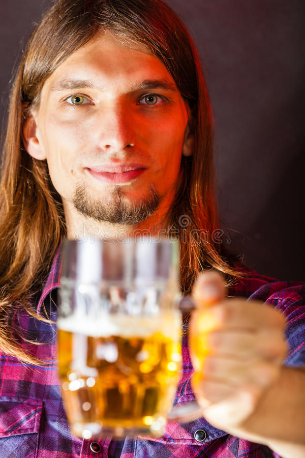 Young man drinking pint. Drinking alcohol liquor relax concept. Young man drinking pint. Male in shirt holding stein with beer stock photography