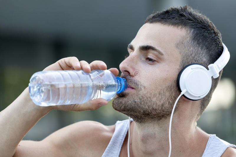 Young man drinking some water from a bottle after training stock images
