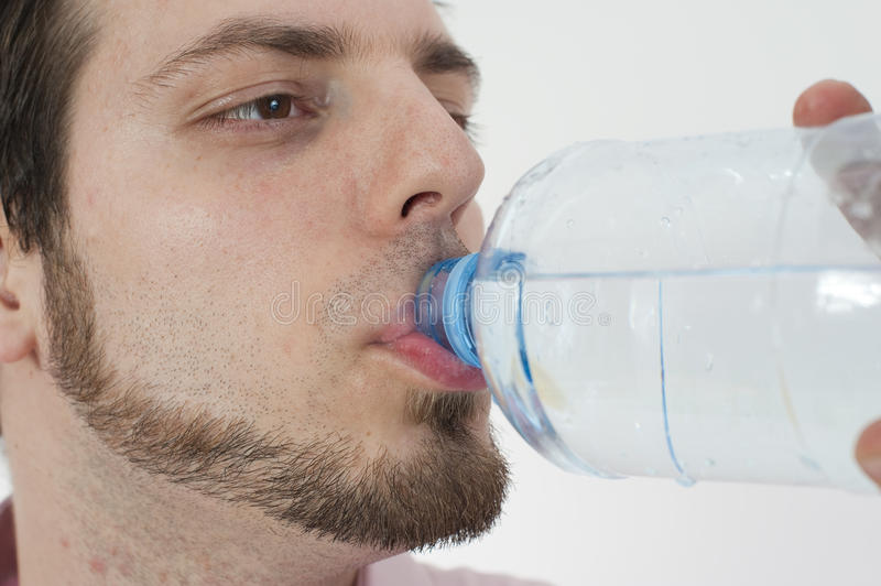 Young man Drinking water from a bottle royalty free stock photography