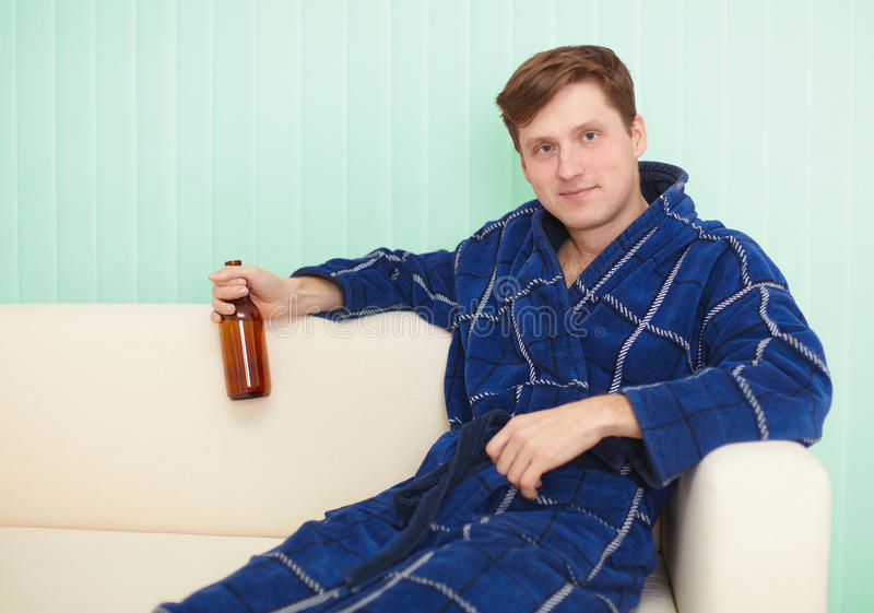 Download Young Man Drinks Beer In Dressing Gown On Sofa Stock Photo - Image: 12250070