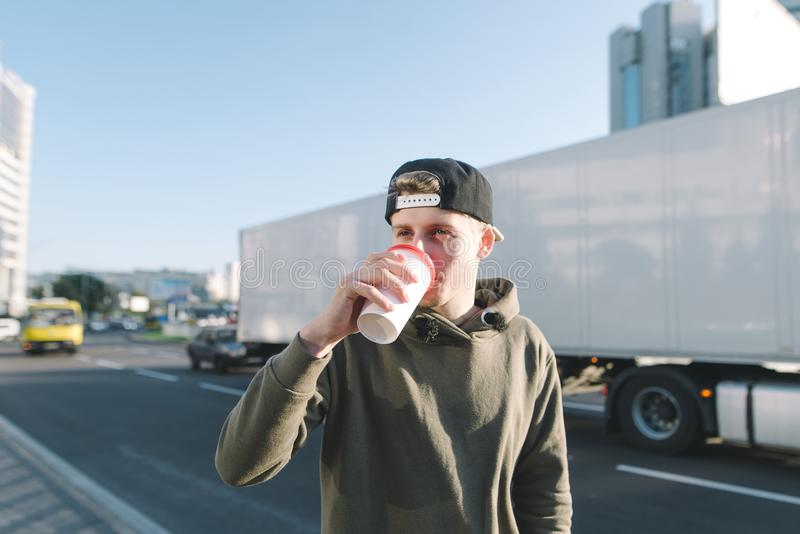 A young man drinks coffee while walking along the streets of the city. The student stands on the background of a road and a white. Large truck royalty free stock photos