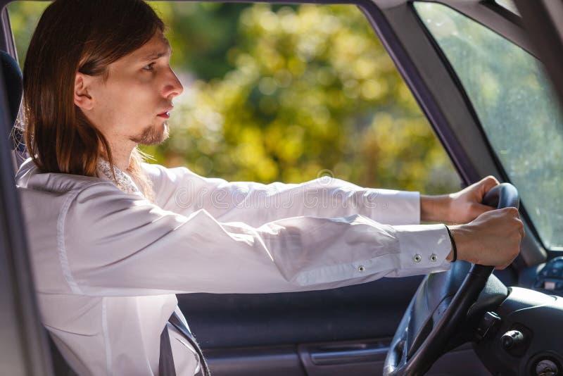 Young elegant metal man driving car. Young man driver wearing white shirt having long hair, driving car carefully royalty free stock photos