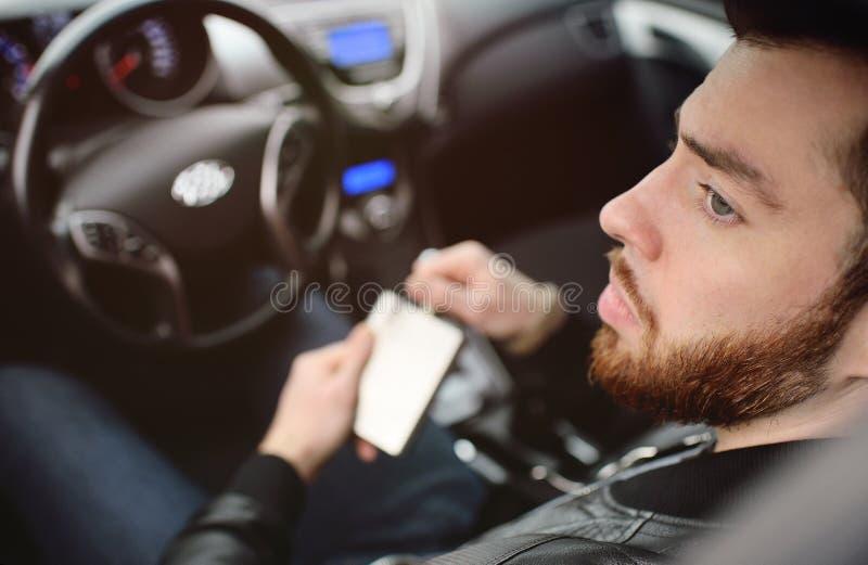 Young man driving a car with an iron flask stock photos