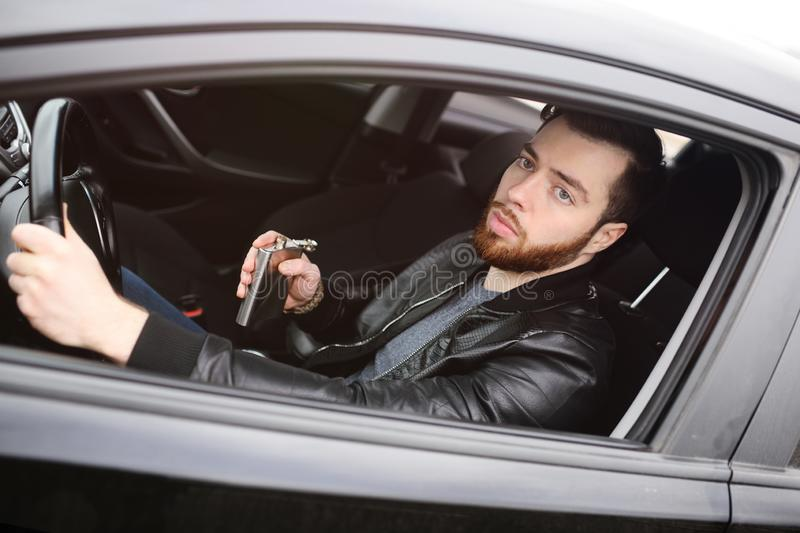 Young man driving a car with an iron flask royalty free stock image