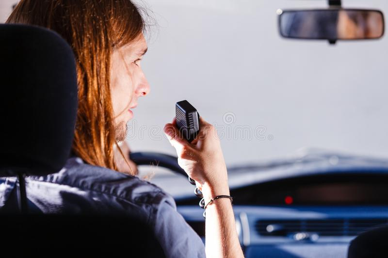 Young man driving car using cb radio. Talking while drive, auto walkie talkie, comunication concept. Young man driving car using cb radio stock image