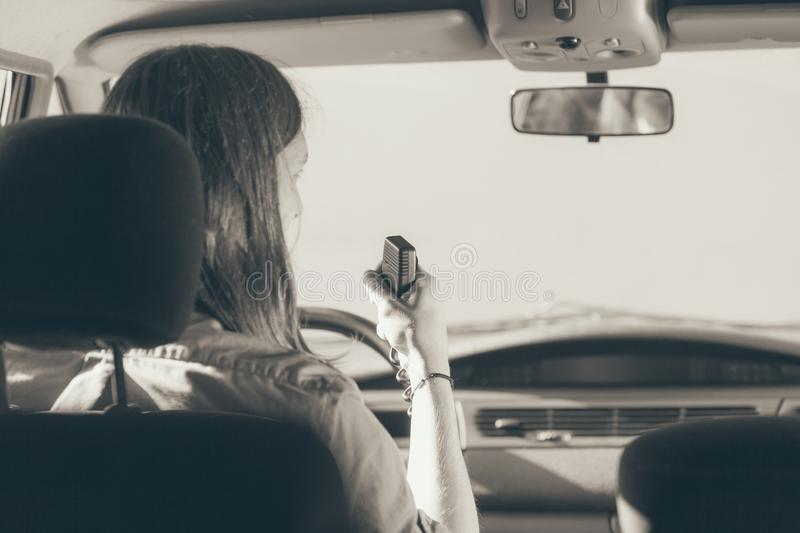 Young man driving car using cb radio. Talking while drive, auto walkie talkie, comunication concept. Young man driving car using cb radio. Black and white photo royalty free stock images
