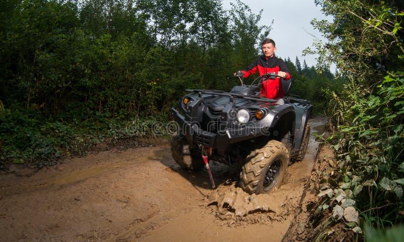 Young man driving four-wheeler ATV through mud. Young guy driving four-wheeler ATV through mud stock images