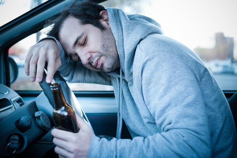 Young man driving his car while drinking alcohol and falling asl stock image