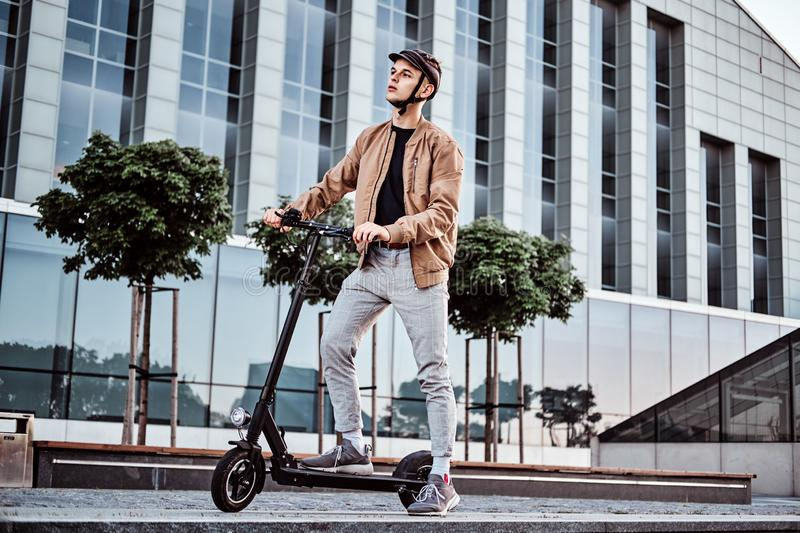 Young man is driving his hew electro scooter. Young attractive student is driving his scooter neat interesting glass building at bright sunny day stock image