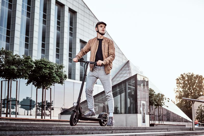 Young man is driving his hew electro scooter. Young attractive student is driving his scooter neat interesting glass building at bright sunny day royalty free stock photo