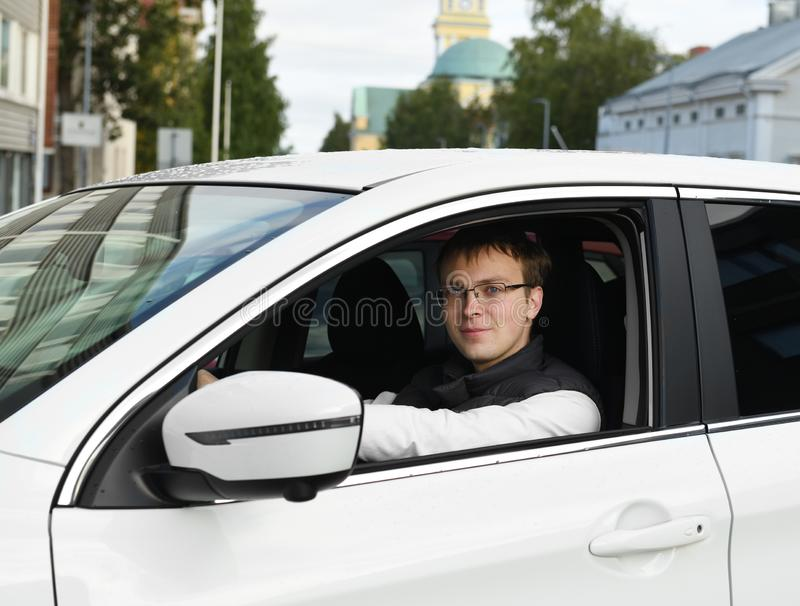 Young man is driving white car. Portrait stock photo