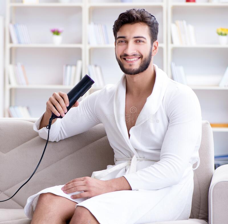 The Young Man Drying Hair At Home With A Hair Dryer Blower