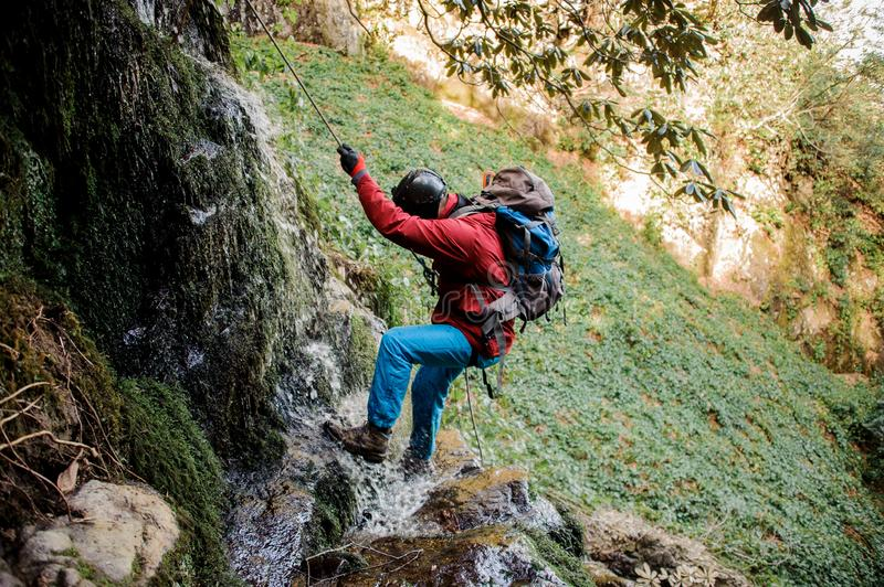 Young man dulfers down the mountain with waterfall in Adjara. Young man in a red jacket with backpack dulfers down the mountain covered in green leaves and small stock image