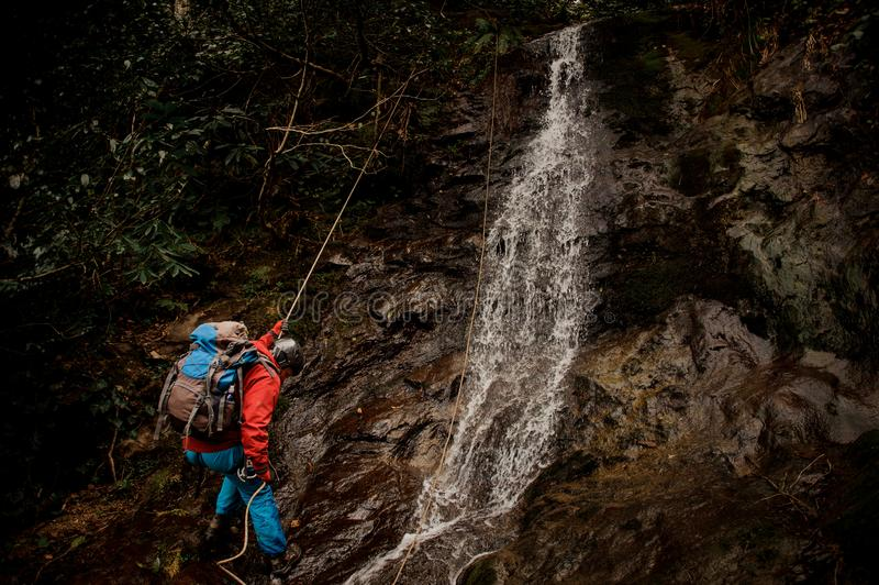 Young man dulfers down the mountain with waterfall in Adjara. Young man in a red jacket with backpack dulfers down the mountains with trees and small beautiful stock images