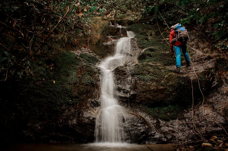 Young man dulfers down the mountain with waterfall in Adjara. Young man in a red jacket with backpack dulfers down the mountains with trees and small beautiful stock photo
