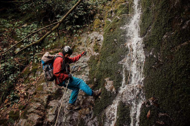Young man dulfers down the mountain with waterfall in Adjara. Young man in a red jacket with backpack dulfers down the mountains with trees and small beautiful royalty free stock image