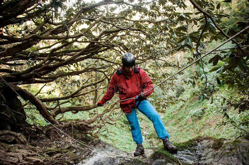 Young man dulfers down the mountains in Adjara. Young man in red jacket dulfers down the mountains in Adjara royalty free stock image
