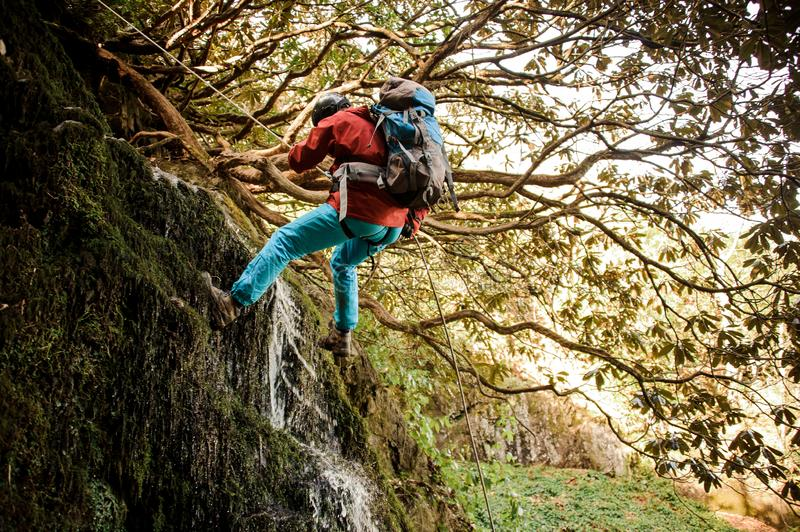 Young man dulfers down the mountains with waterfall in Adjara. Young man in a red jacket with backpack dulfers down the mountains with trees and small beautiful stock image